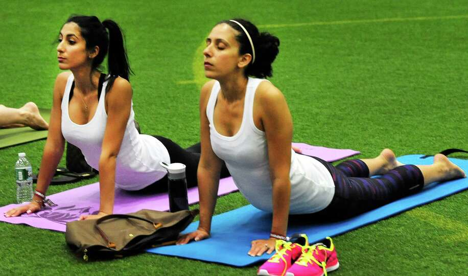 Sondra Alagna, left, and Christine Arconti, practice yoga at the Newtown Yoga Festival sponsored by