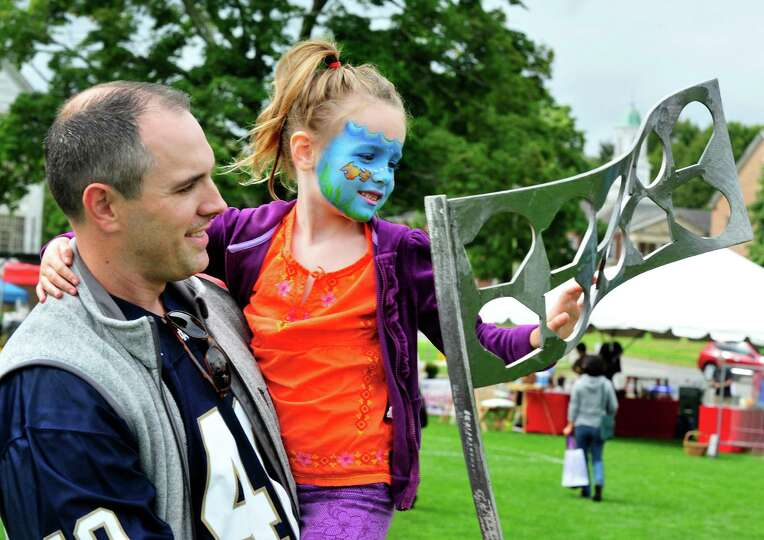 Kyla Frieary, 6, examines a metal sculpture from her dad, Scott's arms, during the Newtown Arts Fest