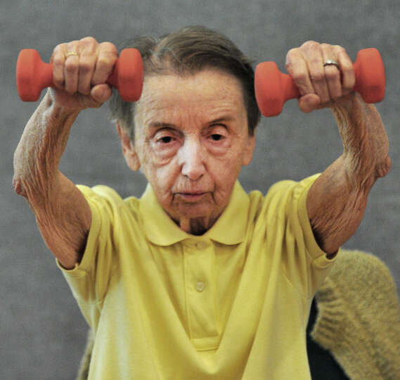 Mary Williams, 92, concentrates on lifting hand weights during Strength Training in the Miry Brook r