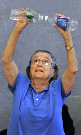 Rita Crimi, 81, may be hoping the water bottles don't leak as she does lifts during Strength Trainin