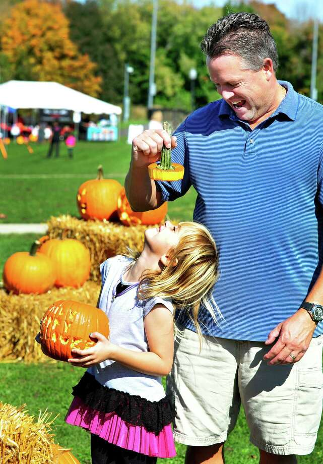 Rob Vanderslice and his daughter, Emily, 7, display their pumpkin at the Newtown Pumpkin Festival on the Fairfield Hills Campus in Newtown, Conn. Saturday, Oct. 12, 2013. Photo: Michael Duffy / The News-Times
