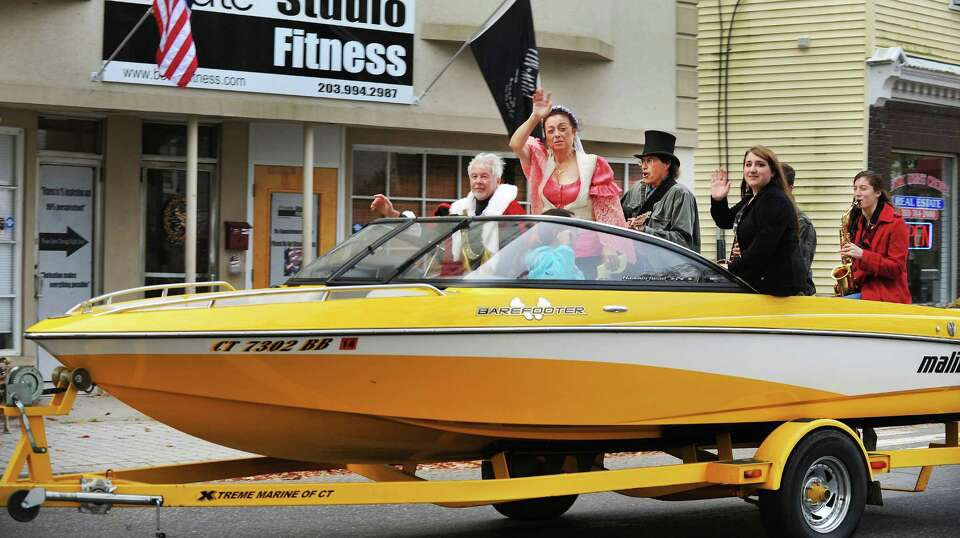 A speedboat races down Greenwood Avenue carrying Rich Zuvich as Christopher Columbus, left, and Gina
