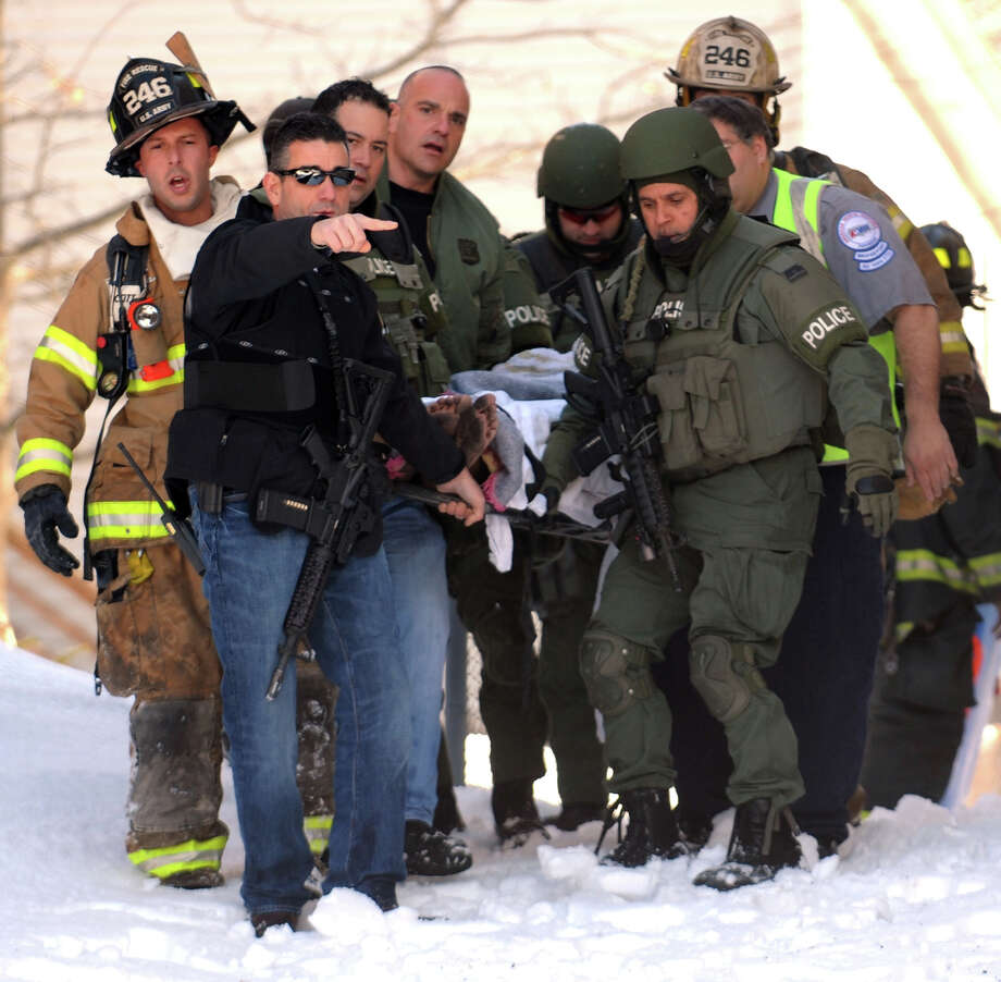 Bridgeport firefighters, police and emergency medical personel work to remove a man following a fire at 158 Robert St. Wednesday morning. Reports that shots had been fired from the house turned out to be false. Photo: Ned Gerard / Connecticut Post