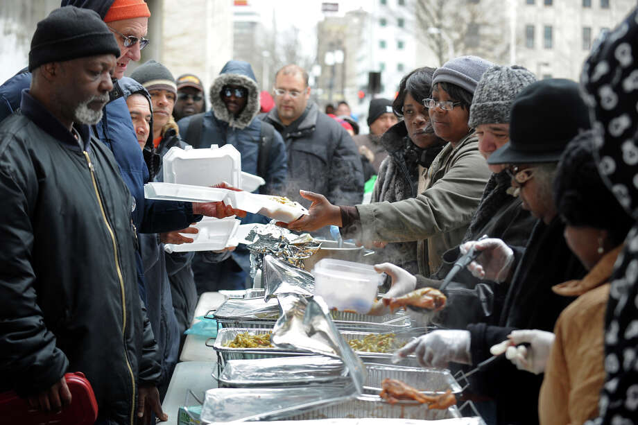A hot meal is served under a highway overpass on John Street, in downtown Bridgeport, Conn., Feb. 24th, 2012. Volunteers are trying to keep the tradition of serving the meal going following the death last month of Ann Marie Tarinelli, who served meals for many years in the same location. Photo: Ned Gerard / Connecticut Post