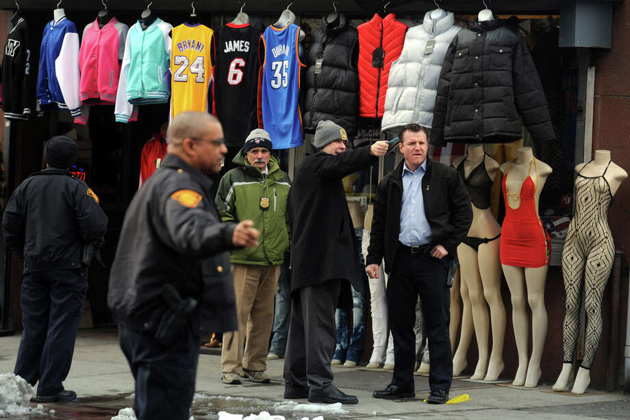 Bridgeport Police Officers investigate the scene Tuesday morning where the owner of East Side Sport, on East Main Street, was shot in an apparent robbery attempt. Felix Reyes, 65, was shot once, but his injuries are not believed to be life-threatening. Photo: Ned Gerard / Connecticut Post