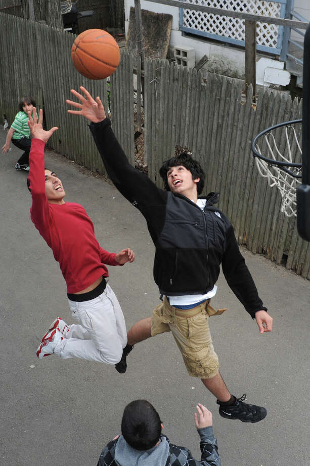 Saman Hassan, left, jumps for a rebound against his brother, Dlier, as they play basketball in the driveway of their Bridgeport, Conn. home, April 23rd, 2013. Photo: Ned Gerard / Connecticut Post