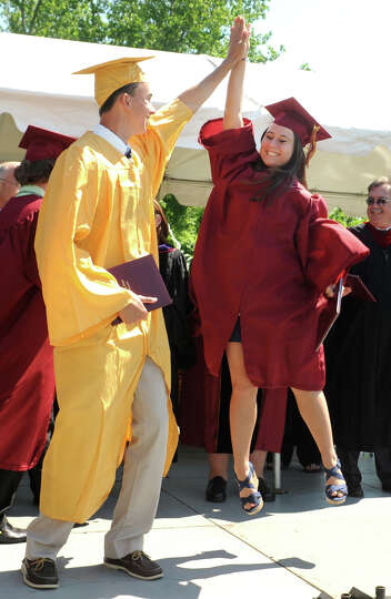 Sophia DeBroff, of Trumbull, jumps to high five fellow graduate Steven D'Ascanio, of Trumbull, durin