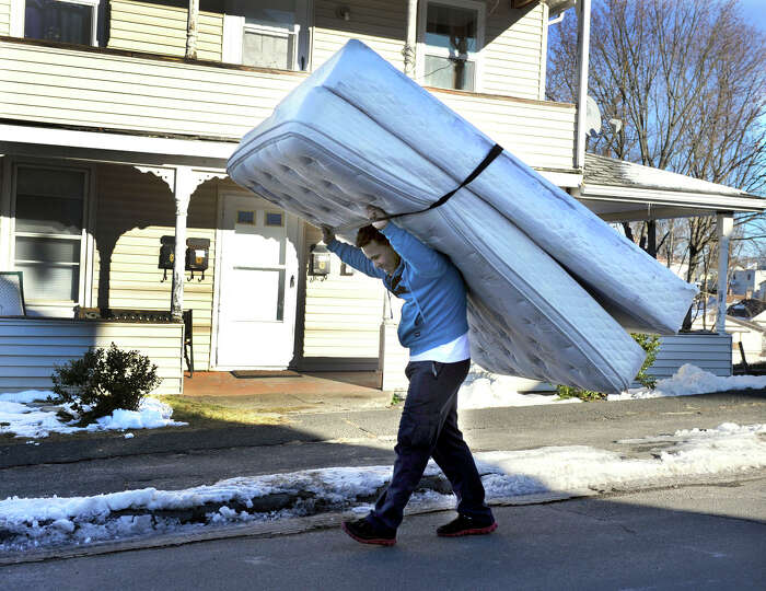 Ramon Tavera, 21, carries his mattress and boxspring to his home on Comstock Street in Danbury, Frid