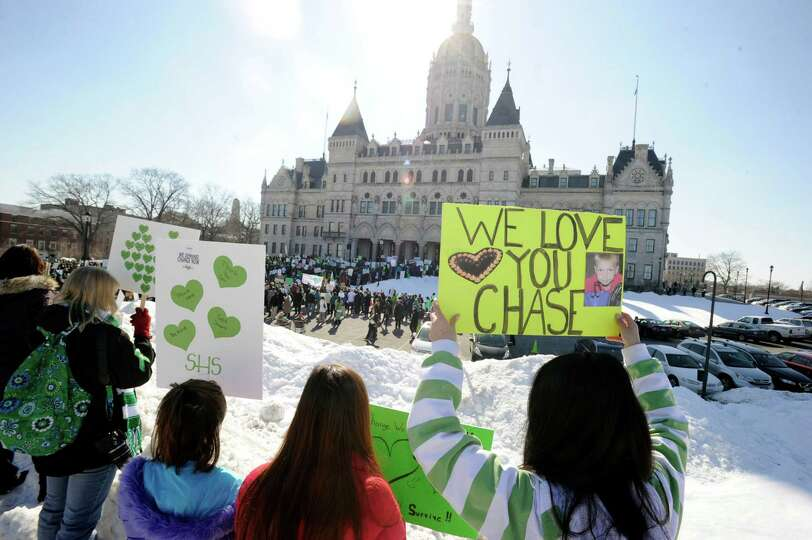 Lindsey Gallagher, right, of Newtown, holds a poster with a photo of family friend, Chase Kowalski,