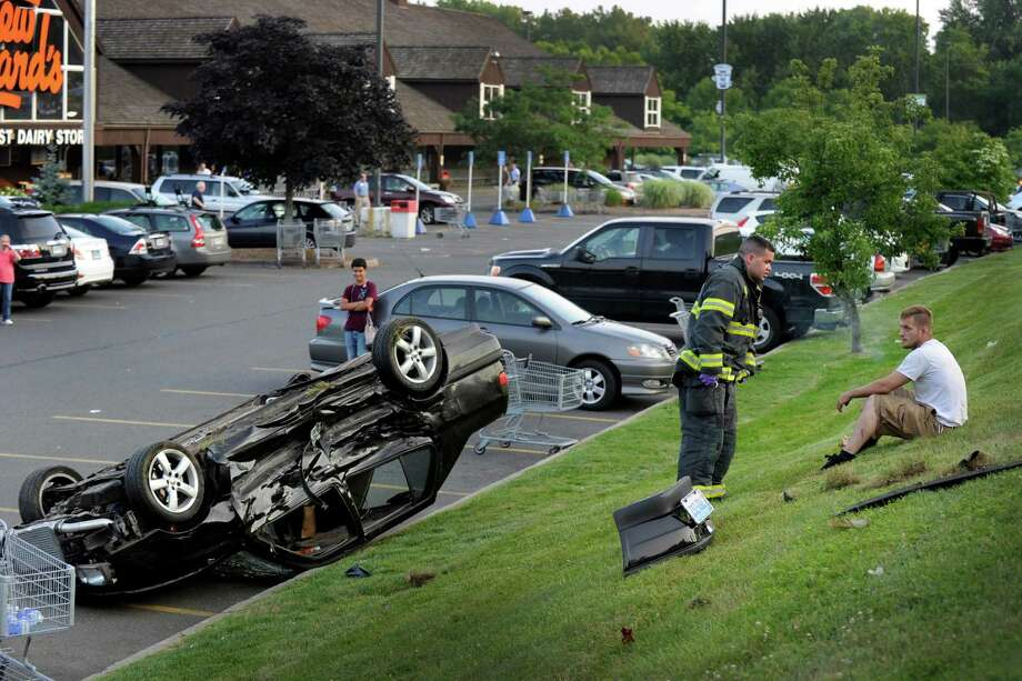 The driver, right, of a car the flipped into the parking lot of Stew Leonard's in Danbury, Conn. Monday, evening, July 8, 2013,  the result of a two-car accident on Federal Road, talks to a fireman. Photo: Carol Kaliff / The News-Times