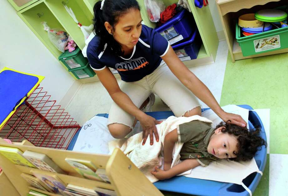Teacher Mery Martins tucks Cristobal Diaz, 3, in for a nap  Wednesday afternoon, July 17, 2013 at Head Start on Foster Street in Danbury, Conn. Head Start has just moved into a brand new building. Photo: Carol Kaliff / The News-Times
