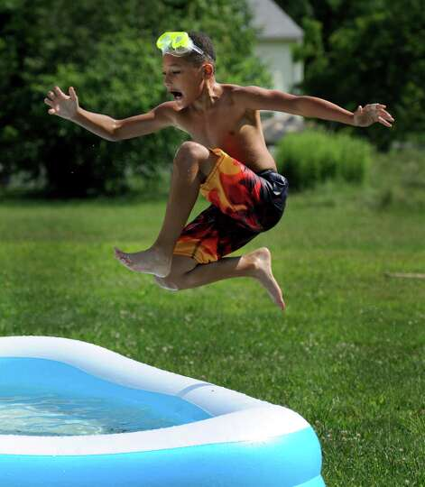Deaven Smith, 9, takes a running leap into the pool in his backyard on Mill Ridge Road in Danbury, C