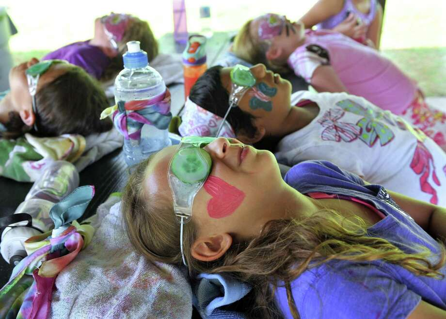 It was Spa Day at Clatter Valley Day Camp in New Milford, Conn., Friday, July 19, 2013. Grace Crispino, 9, of Washington, foreground, joined fellow campers in the pampering experience, which included a cucumber facial and manicure. Photo: Carol Kaliff / The News-Times