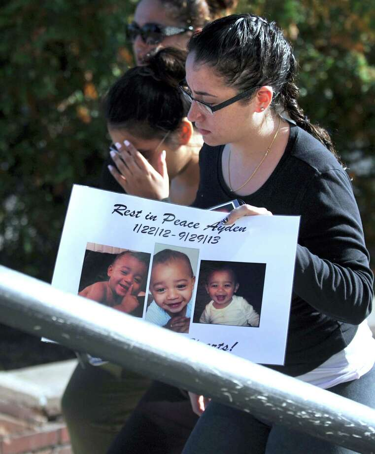 Jacqueline Baskay, the mother of Ayden Baskay, a 19-month-old boy homicide victim, arrives at Danbury Superior Court in Danbury, Conn., Wednesday morning, Oct. 2, 2013,  holding photos of her son and surrounded by supporters. Photo: Carol Kaliff / The News-Times