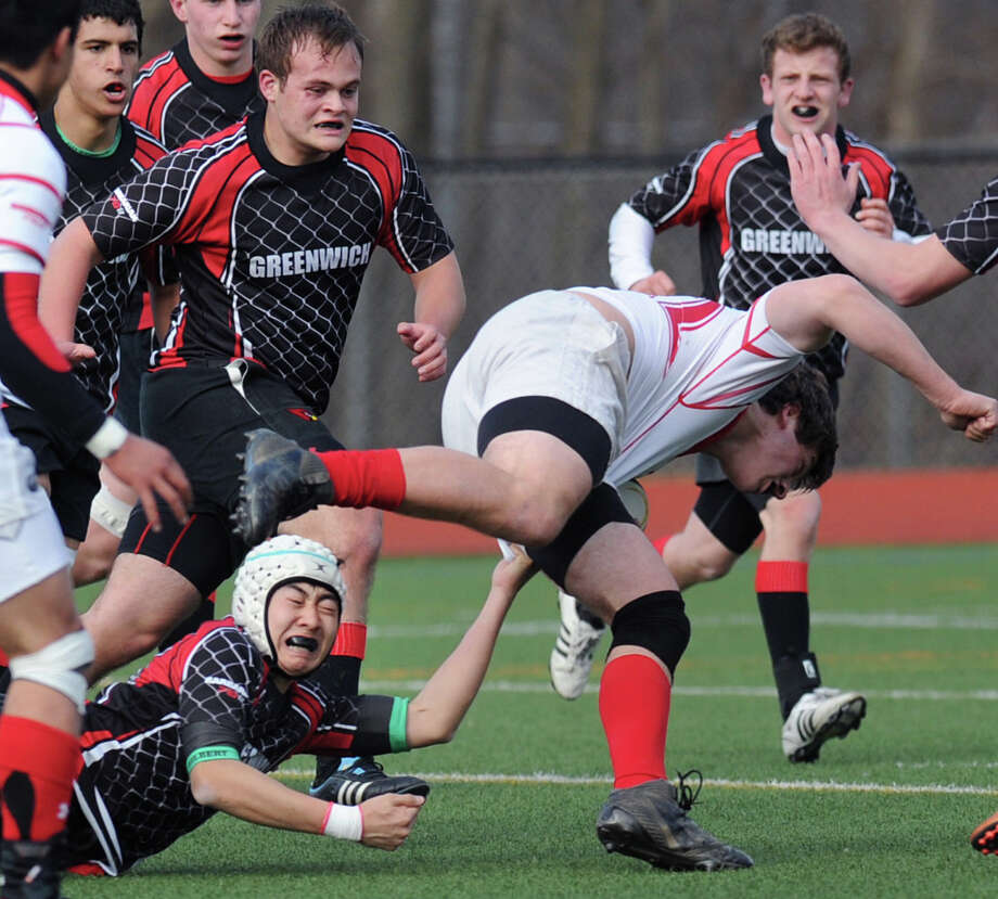 Yoh Nakayama of Greenwich reaches up from the ground to attempt to take down Chris Golger of Fairfield Prep player during the rugby match between Greenwich High School and Fairfield Prep at Greenwich High School, Friday, March 22, 2013. Photo: Bob Luckey / Greenwich Time