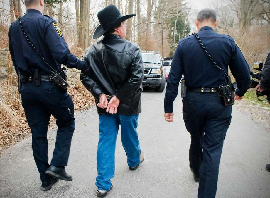 Scott Merrell, former Norwalk mayoral candidate, is taken away in handcuffs by Norwalk police as he is evicted from his house at 6 Woodland Road in Rowayton, Conn. on Tuesday, Feb. 2, 2010. Photo: Kathleen O'Rourke / Stamford Advocate