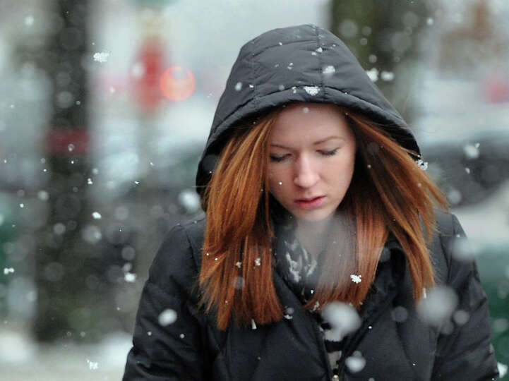 Sarah Cox walks north on Greenwich Avenue during the snow storm that hit Greenwich, Conn., Tuesday a