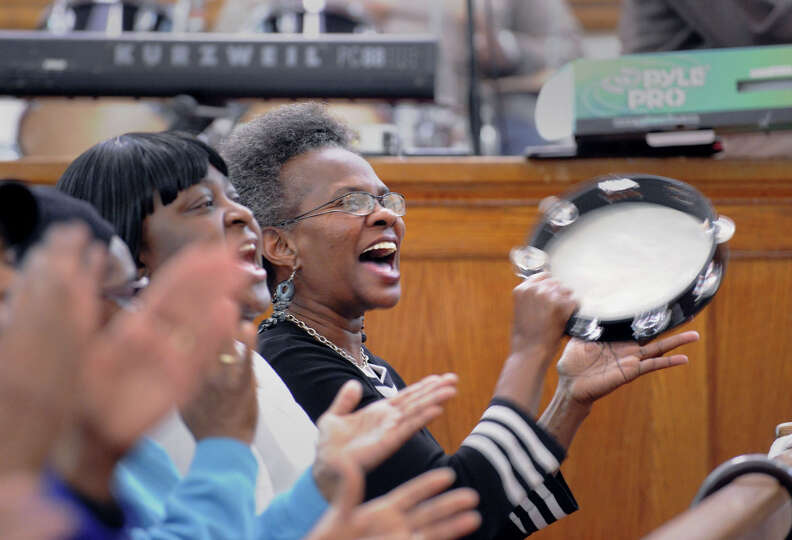 Doreen Harrison plays tambourine while singing during the Faith Tabernacle Inspirational Choir rehea