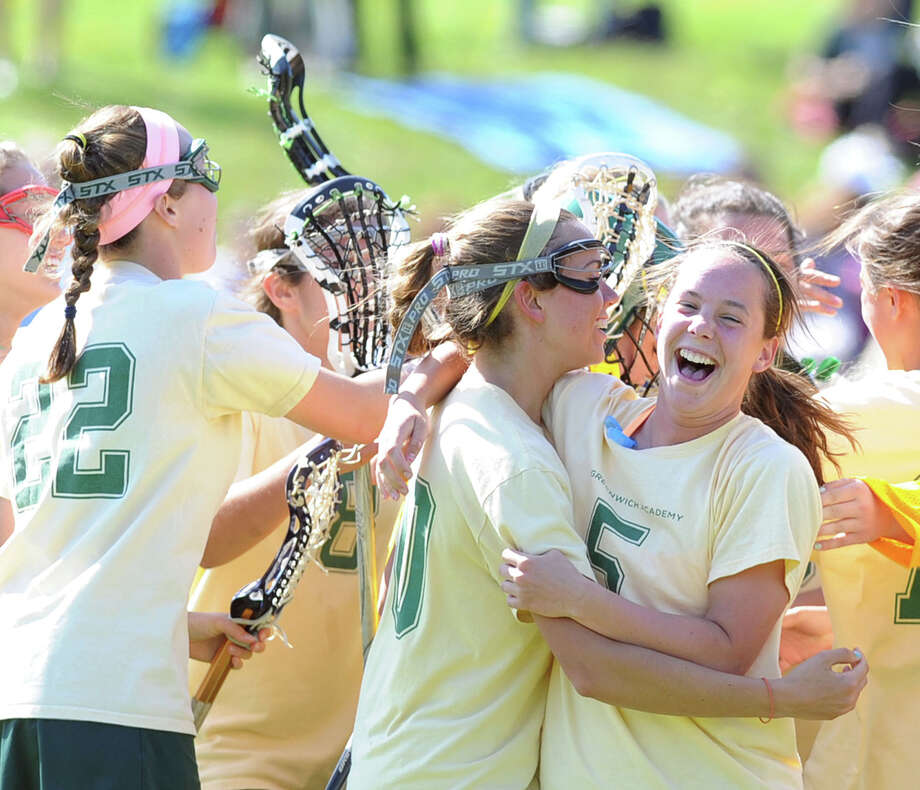 Annie DeFrino of Greenwich Academy, right, hugs teammate, Maggie Schmidt, at the victorious conclusion for Greenwich Academy of the girls high school lacrosse match between Convent of the Sacred Heart and Greenwich Academy at Convent in Greenwich, Saturday afternoon, April 27, 2013. GA defeated Convent, 11-10. Photo: Bob Luckey / Greenwich Time