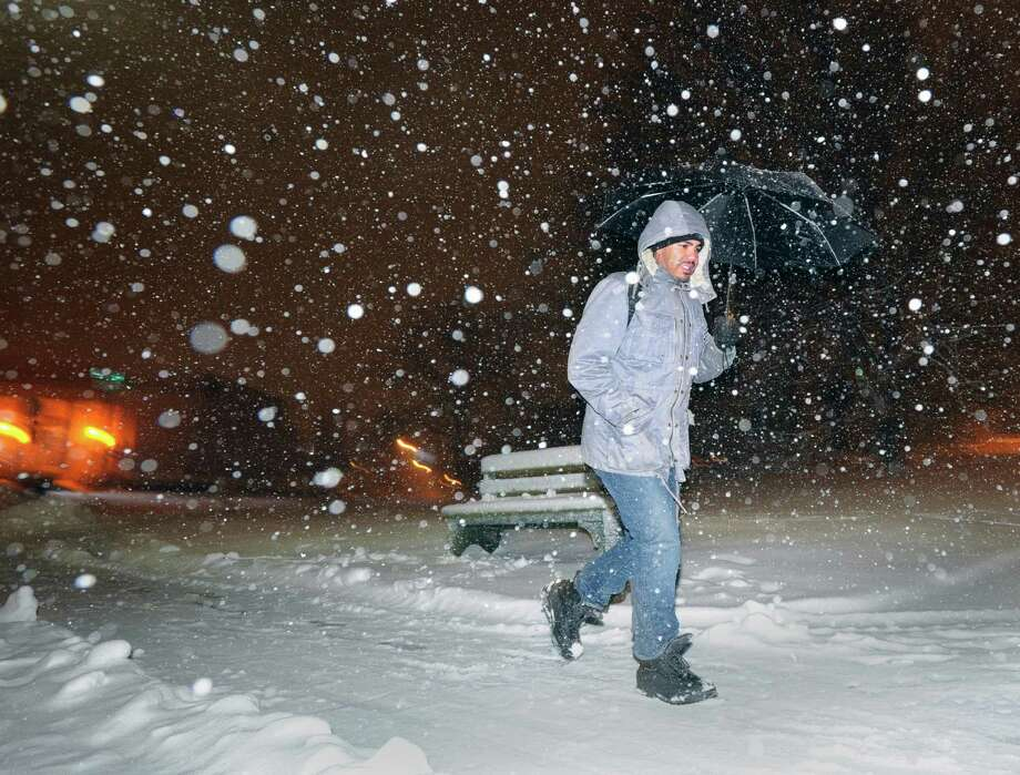 Ray Brown of New Jersey heads north on Greenwich Avenue during the snowstorm that hit Greenwich, Conn., Friday night, Feb. 8, 2013. Brown said he took the train into town to help his girlfriend get home during the storm. Brown said she works at Greenwich Hospital. Photo: Bob Luckey / Greenwich Time