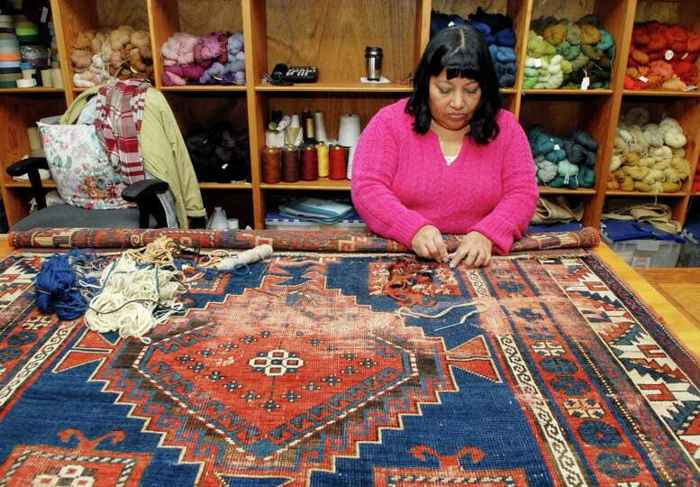 Olga Mendez works on repairing a oriental rug at Triple S carpet cleaners in Stamford, Conn. on Mond