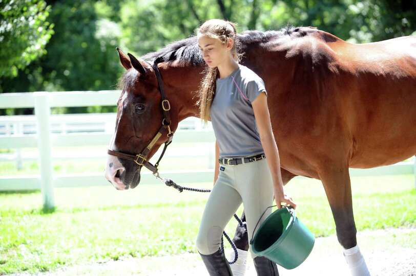 Sloan Jocoby, 13, walks with a brown horse at Country Lane Farm's Round Hill Barn, in Greenwich, Con
