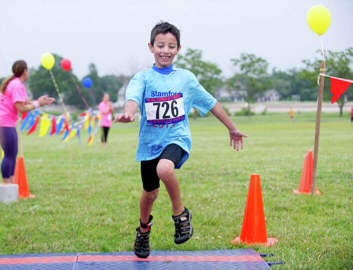 Chris Gervasi, 7, crosses the finish line at the end of Saturday's KIC-IT kid's triathalon at Cove I