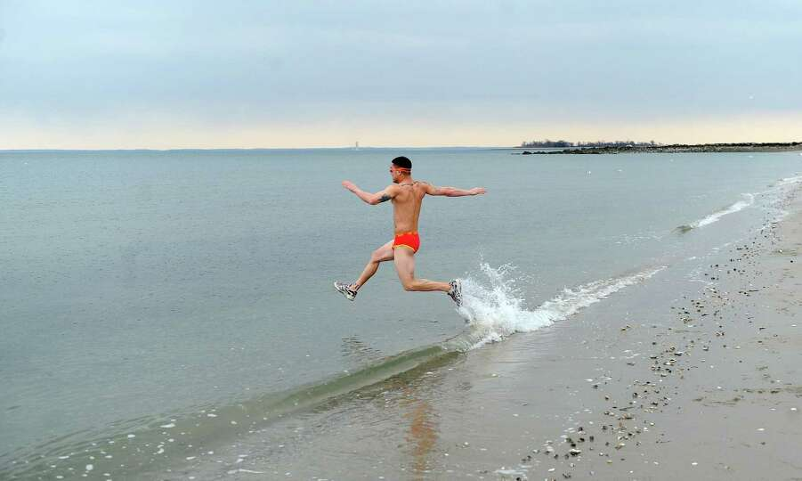 Ken Ildefonso is the first to run into the Long Island Sound at Compo Beach in Westport, Conn., duri