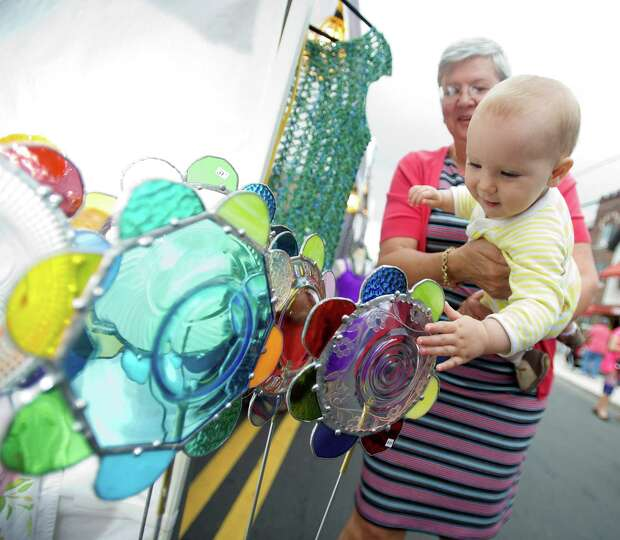Tatiana Belykh holds her 11-month-old granddaughter, Mijanou, as they look at art at the Summer Glas