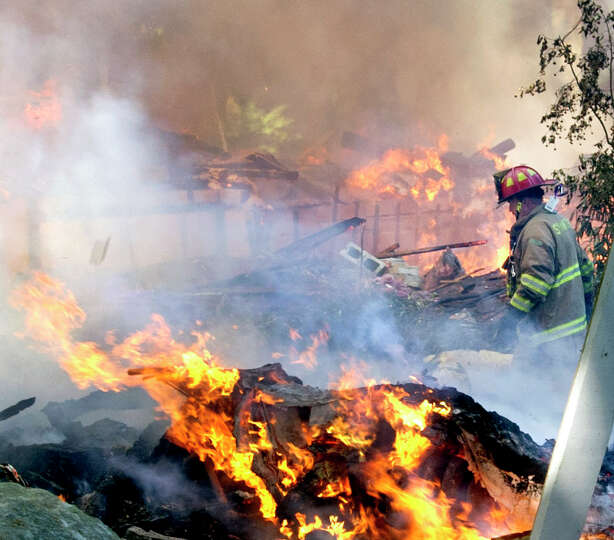 A firefighter walks through the burning rubble of 305 Webbs Hill Road in Stamford, Conn., where the