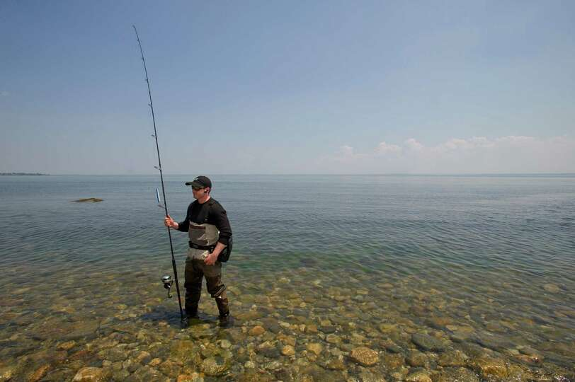 Gregory McNamara fishes in the water of the Long Island Sound at Shippan Point in Stamford, Conn., o