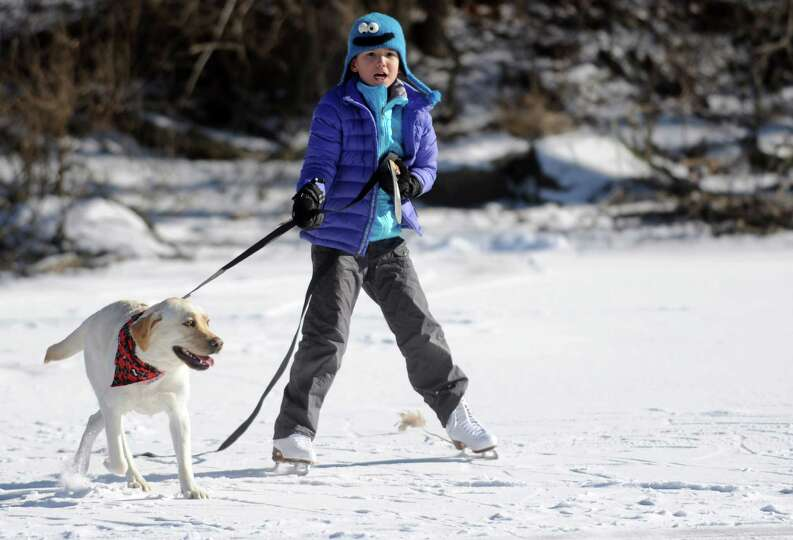 Mimi Sue Novak, 8, gets a pull from Millie as she skates on Gorham's Pond in Darien on Saturday, Jan