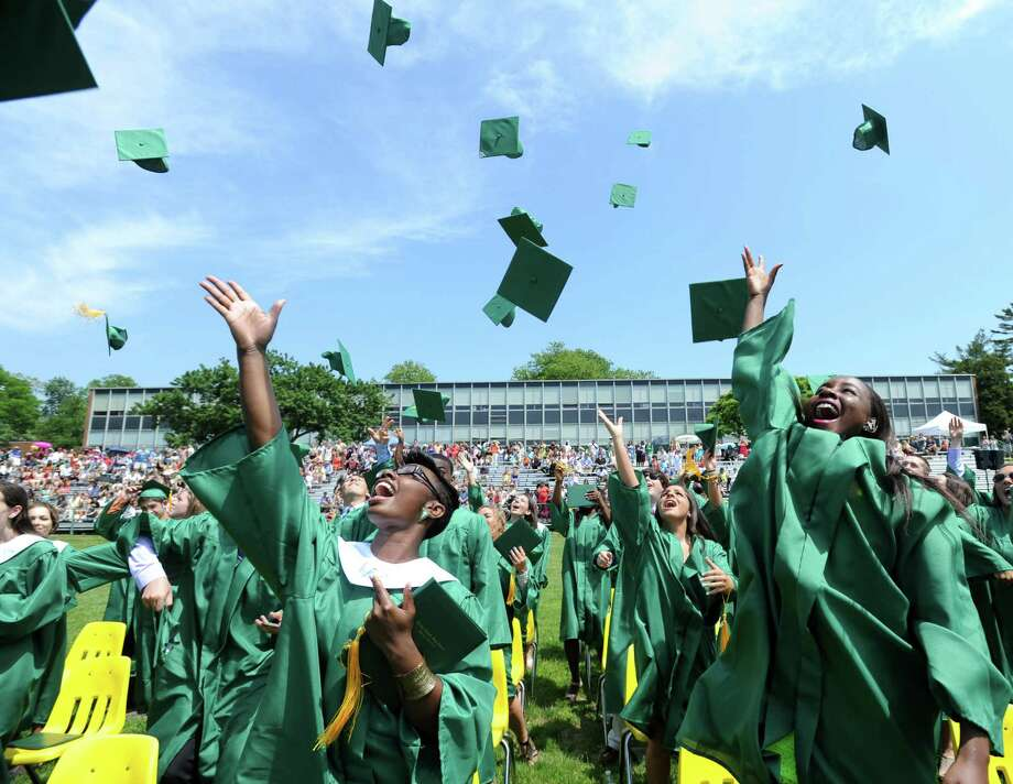 Graduates throw their hats during Saturday's commencement ceremony for Trinity High School graduates on June 1, 2013. Photo: Lindsay Perry / Stamford Advocate