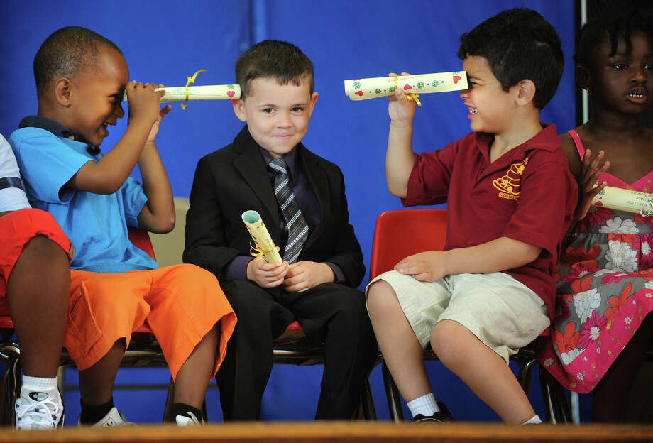 From left; Shane Davis, 5, Dennis King, Jr., 5, and Robert Bauza, 4, find creative uses for their graduation certificates as they sit on stage for their Pre-K graduation ceremony at St. Ambrose School in Bridgeport, Conn. on Tuesday, June 18, 2013. St. Ambrose School is being closed by the Bridgeport Diocese at the end of the school year. Photo: Brian A. Pounds / Connecticut Post