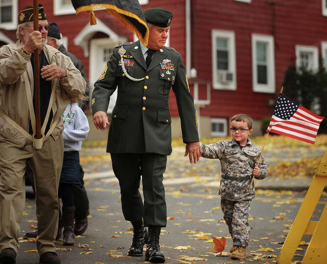 Wyatt Gaffney, 3, marches with his grandfather, Vietnam veteran Tom Johnson, of Milford, in the Vete
