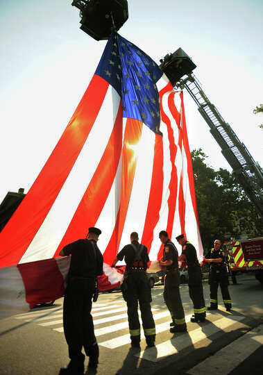 Bridgeport firefighters work as a team to fold a giant American flag hung between two ladder trucks