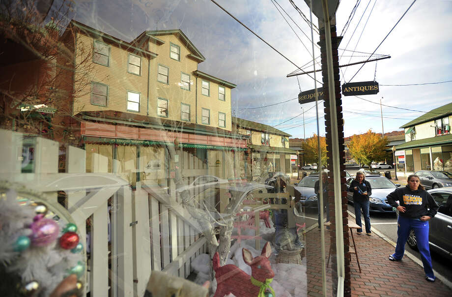 A large antiques store is reflected in a store window with an inviting Christmas theme on the walker-friendly Bank Street in downtown Seymour, Conn. on Sunday, November 3, 2013. Photo: Brian A. Pounds / Connecticut Post