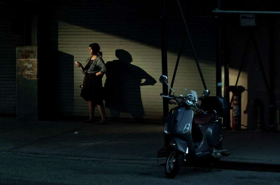 Light is reflected onto a woman checking her phone along 26th Street in the Chelsea section of New York, N.Y., on Sept. 5, 2013. Photo: Jason Rearick / Stamford Advocate