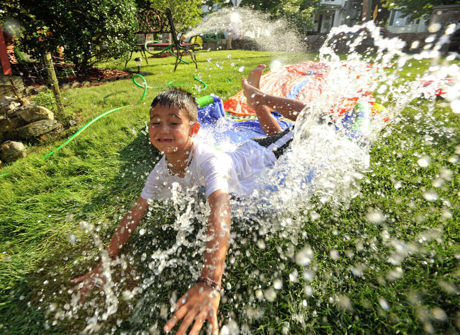 Adrian Hernandez, 5, slides into a pool of water to cool off in Stamford on Monday, July 15, 2013. Temperatures on Monday reached into the 90s with temperatures forecasted to remain there throughout the week. The high heat paired with high humidity could make it feel as hot as 100 degrees. Photo: Jason Rearick / Stamford Advocate