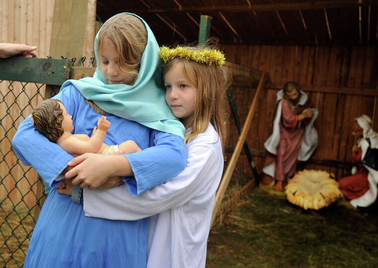Holding a doll representing the baby Jesus, Jennie Olmsted, dressed as the Virgin Mary, is hugged by