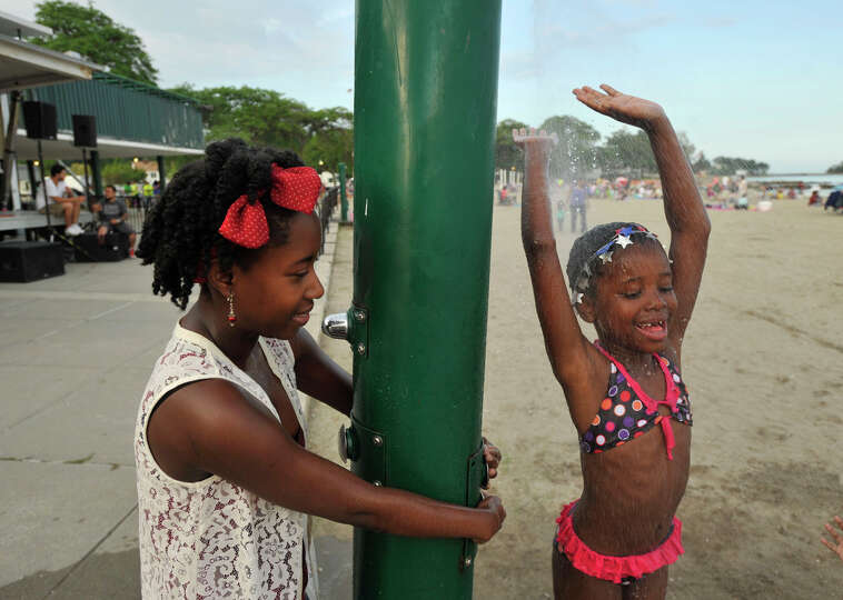 Audrienne Brissett, left, keeps the shower on for her neice Naia Brissett before the fireworks show