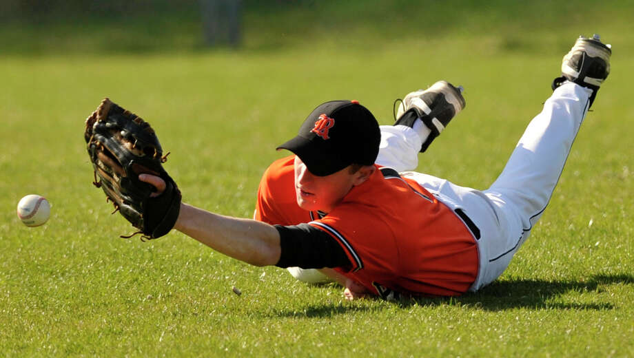 Ridgefield right fielder Robert DePalma narrowly misses a diving catch during the Tigers' game against Greenwich at Greenwich High School on Monday, April 15, 2013. Greenwich won, 8-5. Photo: Jason Rearick / Stamford Advocate