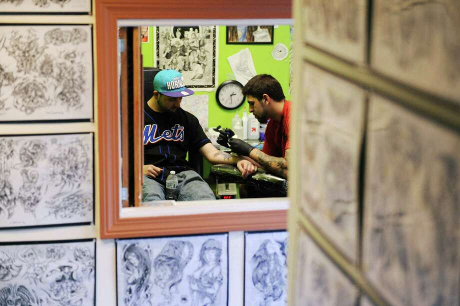 Steve Newman, of Danbury, gets tattoed by Mathew Leibowitz at The Iron Butterfly tattoo parlor in Danbury, Conn. on Wednesday, May 22, 2013.  Connecticut Congress is in the process of passing legislation that would require tattoo artists to take a training program, pass an exam and pay a $250 license fee.  The shop's owner, Annette Mathews, disagrees with the legislation. Photo: Tyler Sizemore / The News-Times