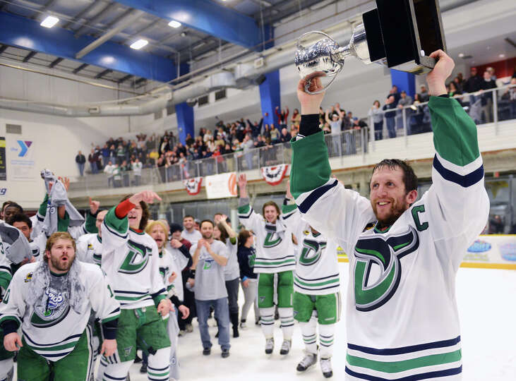 Danbury's Ed Campbell hoists the Commissioner's Cup above his head after the Danbury Whalers defeate
