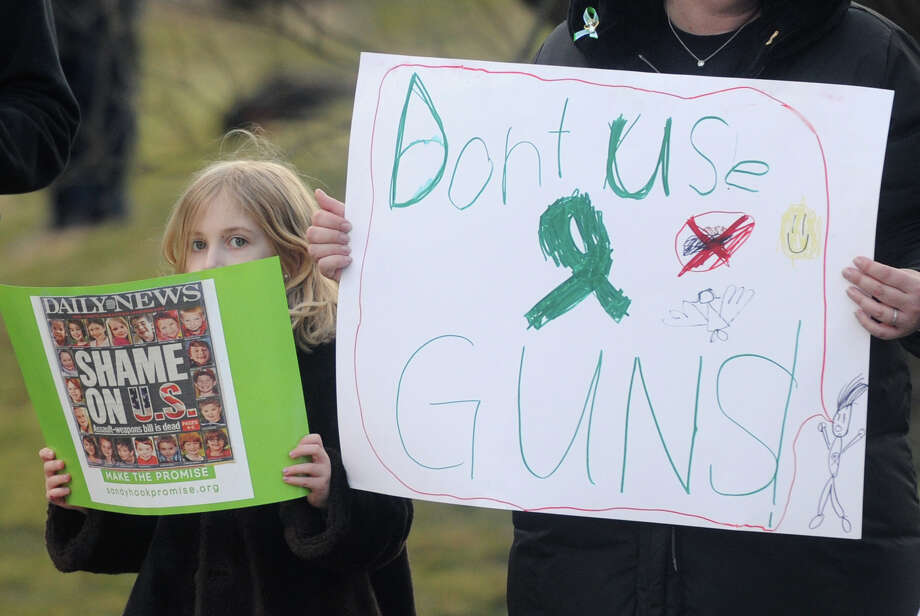 Lauren Mileram, a first-grader at Sandy Hook Elementary School, hold a sign next to her mother, Erin Mileram, of Sandy Hook, at the Newtown Action Alliance rally outside of the National Shooting Sports Foundation headquarters in Newtown, Conn. on Thursday, March 28, 2013.  The rally was attended by supporters of gun reform, as well as many members of the NRA.  The two groups cooperated peacefully together, with gun reform supporters outnumbering NRA supporters by about a two to one ratio.  More than 100 combined demonstrators attended the rally. Photo: Tyler Sizemore / The News-Times