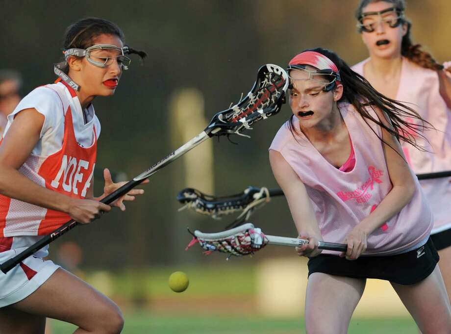 Greenwich's Natalie Paletta, left, hits Ridgefield's Maggie Scalzo in the face while fighting for the ball during Ridgefield's 12-11 win over Greenwich in girls lacrosse at Ridgefield High School in Ridgefield, Conn. on Thursday, May 2, 2013. Photo: Tyler Sizemore / The News-Times