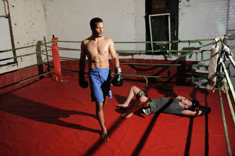 Boxing club trainer Santos Escribano, Jr., left, walks away after a round of sparring with Geoffrey