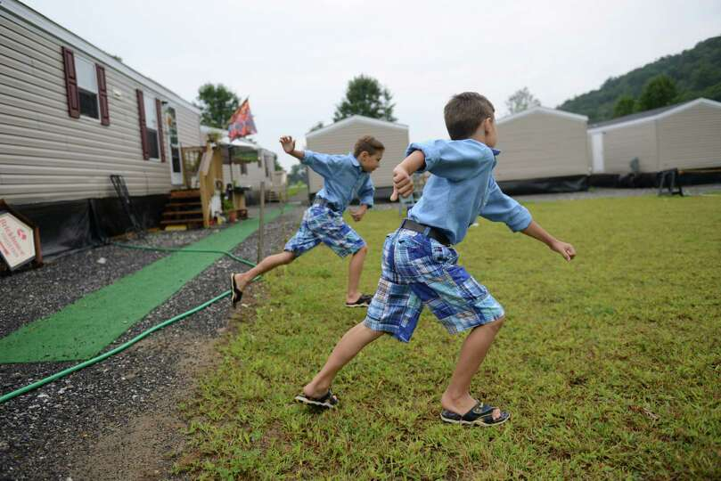 Ivan Kalashnikov, left, 8, and his brother Alexander Kalashnikov, 6, play outside their mobile home
