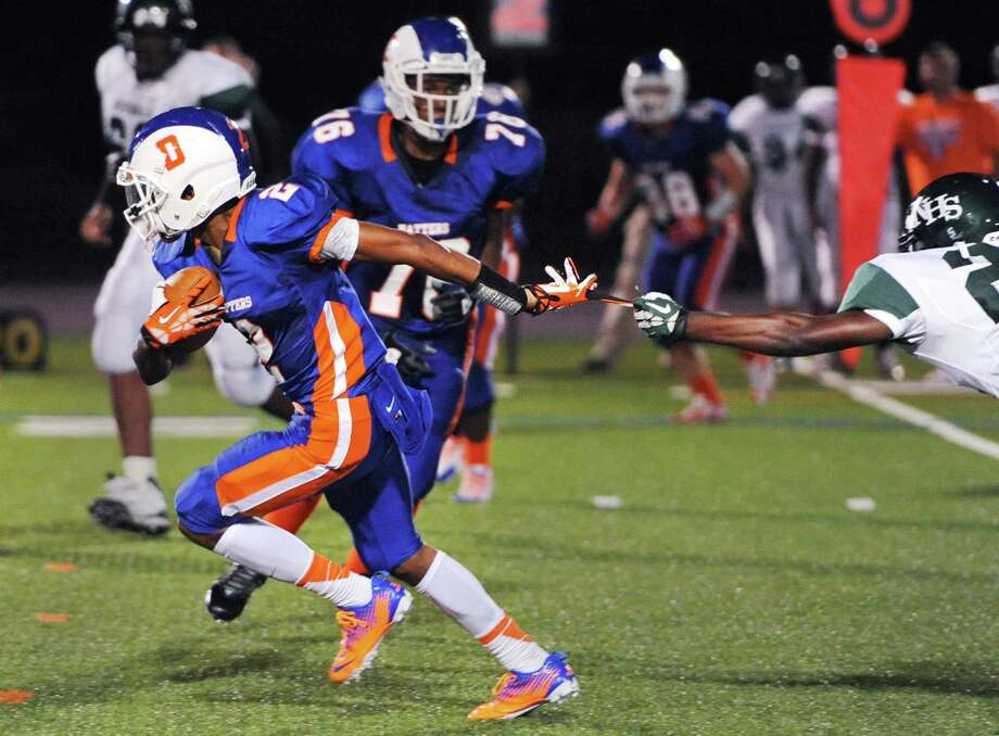 Danbury's Elijah Duffy, left, breaks away as Norwalk defender Hopeton Chambers grabs at his glove in the FCIAC high school football game between Danbury and Norwalk at Danbury High School in Danbury, Conn. on Friday, Sept. 20, 2013. Photo: Tyler Sizemore / The News-Times