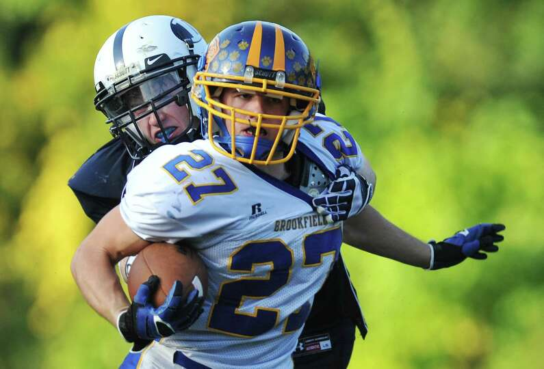 Brookfield's Matthew Melby (27) avoids a tackle by Immaculate defender Michael Woods in the SWC high